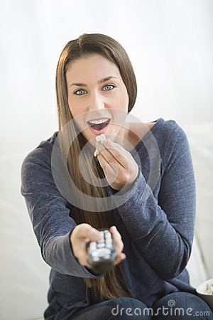 Surprised Woman Eating Popcorn While Watching TV