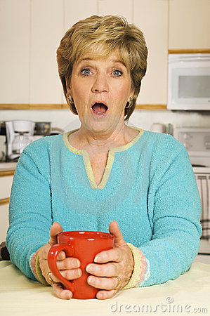 Surprised woman holding coffee mug in kitchen