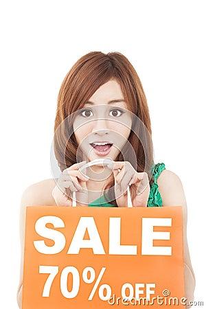 Surprised  woman showing shopping bag