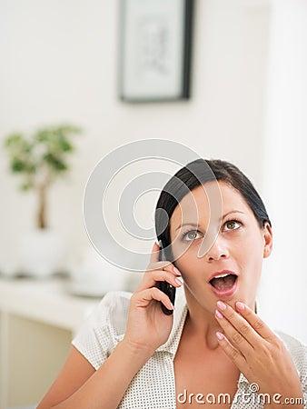 Surprised woman speaking mobile phone
