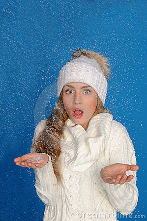 Surprised woman in winter clothes under snow