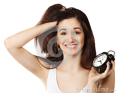 Surprised young brunette woman holding clock