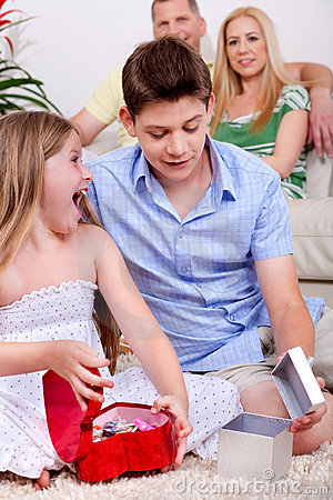 Surprised young kids with gift boxes sitting