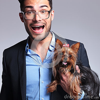 Surprised young man holds puppy