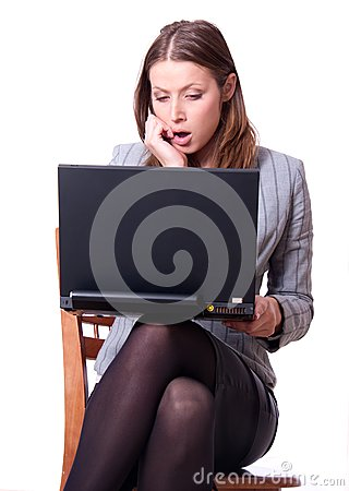 Surprised young woman with laptop on her knee.