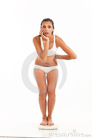 Surprised young woman on scale