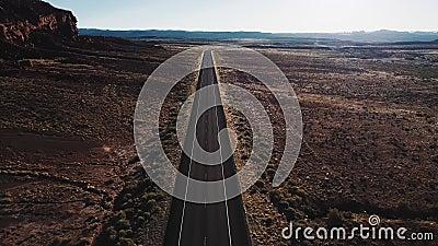 Surr som flyger framåtriktat över den raka ökenhuvudvägvägen i USA vildmarken nära det massiva steniga berget och härlig himmel lager videofilmer