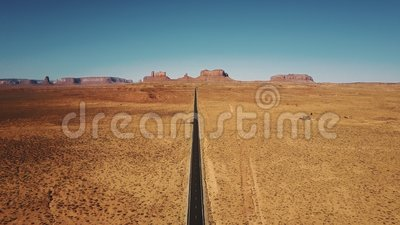 Surr som tillbaka högt flyger ovanför den tomma sandstenökenvägen i monument dal, Arizona med plan berghorisont arkivfilmer