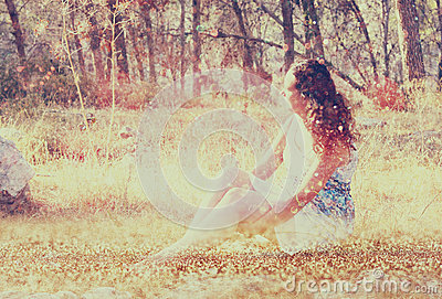 Surreal blurred background of young woman sitting on the stone in forest. abstract and dreamy concept. image is textured and retro