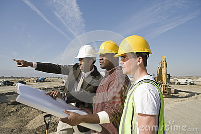 Surveyor And Construction Workers With Plans On Site