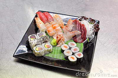 Sushi on black plate and metal background