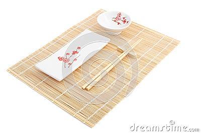 Sushi plates and chopsticks on bamboo mat