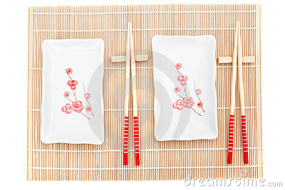 Sushi plates and chopsticks on bamboo mat