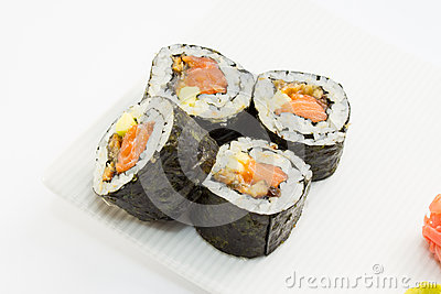 Sushi roll in nori with ginger and wasabi on white plate