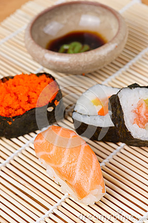 Sushi and soy sauce on bamboo mat