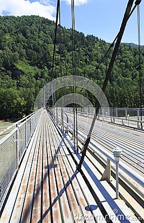 Suspension bridge across mountain river Katun. Altai.