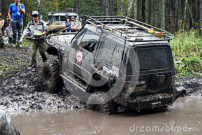SUV overcomes mud obstacles. Editorial Stock Image
