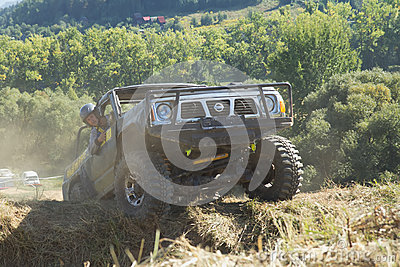 SUV is overcoming a terrain obstacles. Editorial Stock Photo