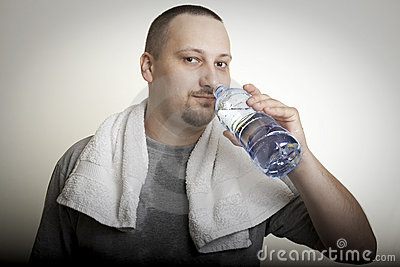 Sweaty man drinking water after exercise
