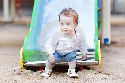 Sweet baby girl with blue eyes playing on slide