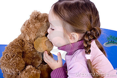 A sweet baby girl kiss her teddy