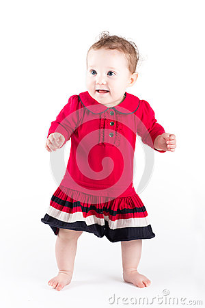 Sweet baby girl in red dress making her first steps