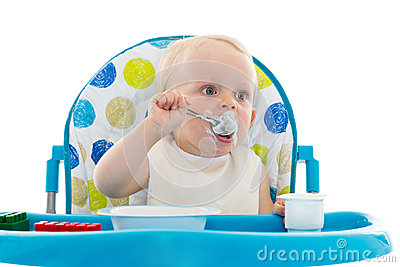 Sweet baby with spoon eats the yogurt.