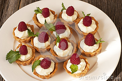 Sweet baskets with cream and raspberries and blueberry