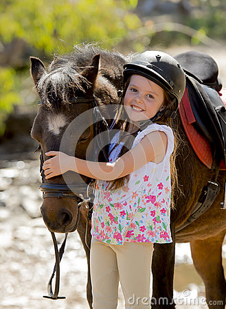 Free Sweet Beautiful Young Girl 7 Or 8 Years Old Hugging Head Of Little Pony Horse Smiling Happy Wearing Safety Jockey Helmet In Summer Royalty Free Stock Photo - 53444435