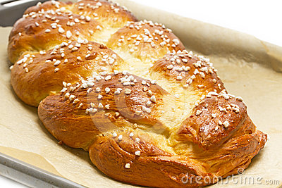Sweet braided bread on a baking tray