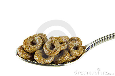 Sweet brown rings on teaspoon isolated on white