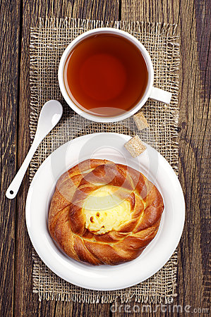 Sweet bun with cream and tea