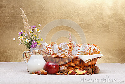 Sweet cakes in basket, fruit and milk decoration