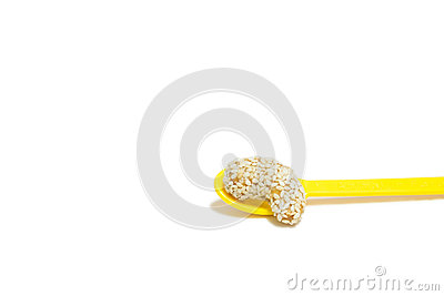 Sweet cashew nut with sesame on yellow spoon