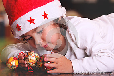 Sweet child plays with xmas tree balls
