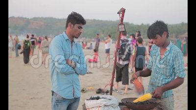 Sweet corn on fire. Corn on the cob on a beach food stand in India stock video