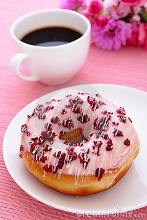 Sweet cranberry donut with a cup of coffee