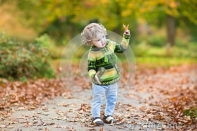Sweet curly baby girl dancing in autumn park