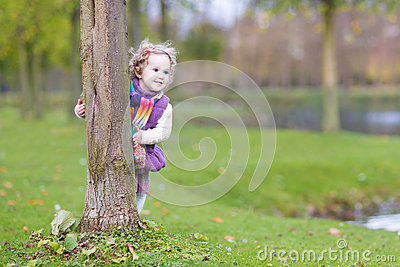 Sweet funny toddler girl hiding behind tree in park