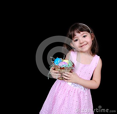 Sweet girl holding basket of bright easter