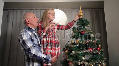Sweet little girl adjusting Christmas tree top. stock footage