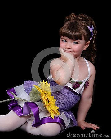 Sweet little girl in ballet outfit sitting with