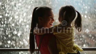 Sweet Little Girl is Hugging and Kissing Her Beautiful Young Mom. Happy Mothers Day. Waterfall is on Background. Sweet Little Girl is Hugging and Kissing Her stock footage
