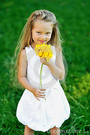 Sweet little girl with smell flower in a park