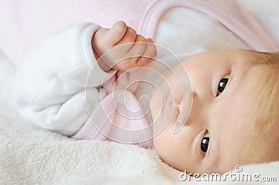 Sweet little newborn baby in a bed