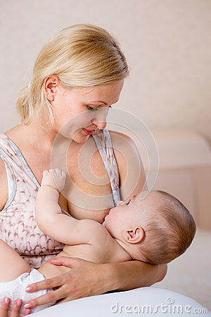 Sweet mother breast feeding her infant baby