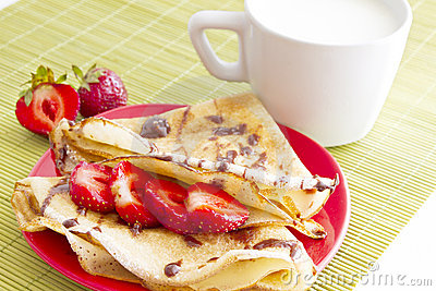 Sweet pancakes with strawberry and cup of milk