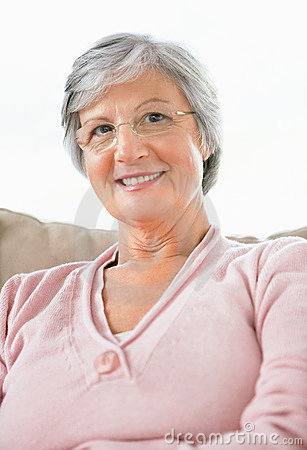 Sweet retired woman sitting on a couch