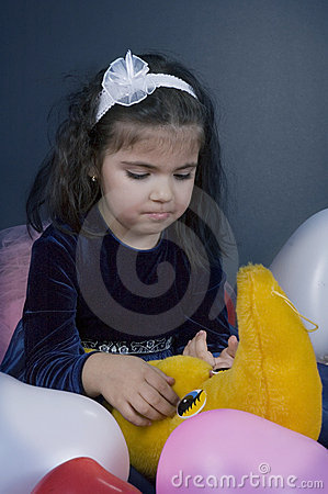 Sweet and sad young girl playing with her plush moon