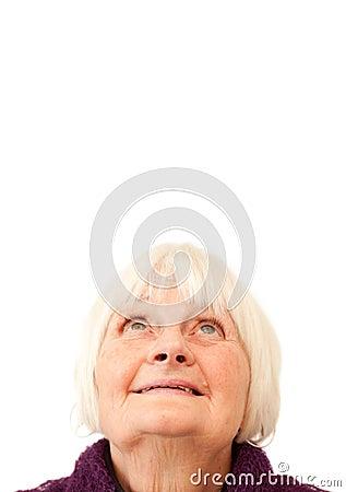 Sweet senior woman looking up at copyspace